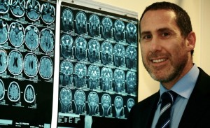 Dr Silber standing next to a brain scan